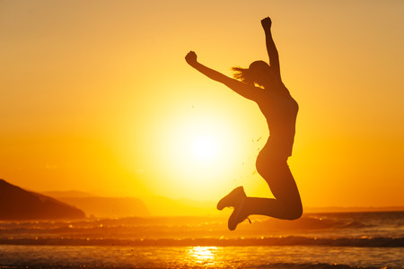 Silhouette of happy joyful woman jumping and having fun at the beach against the sunset. Freedom and leisure vacation concept.