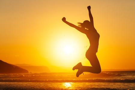 Silueta de feliz saltando mujer alegre y que se divierte en la playa contra la puesta de sol. La libertad y el concepto de vacaciones de ocio.