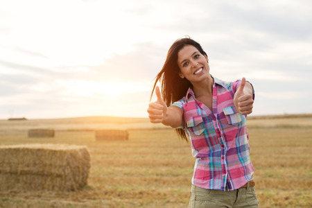Countryside successful woman at harvested wheat field. Farming and rural agriculture business success concept.