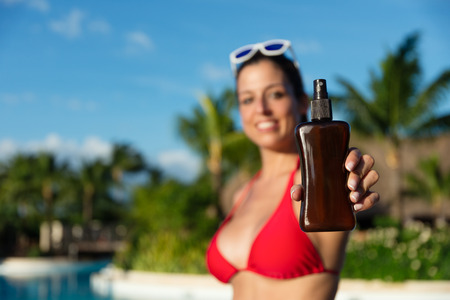 foreground focus: Detail of woman holding a sunscreen or suntan lotion at resort hotel swimming pool on summer. Skin care and protection against the sun concept. Focus on foreground. Stock Photo