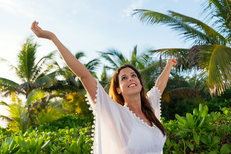 outstretching: Summer leisure and relax. Blissful woman on tropical vacation relaxing.