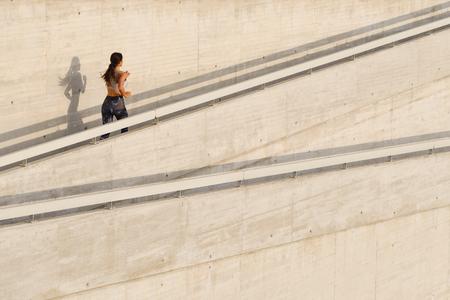 Deportivo fitness joven corriendo por una rampa urbana. Entrenamiento femenino del corredor apto fuera. Foto de archivo - 77591339