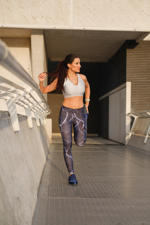 Motivated sporty woman stretching legs for warming up before urban outdoor fitness and running workout.