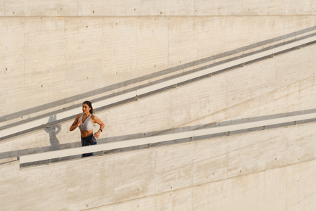 Sporty fitness young woman running up and urban ramp. Female fit runner training outside.