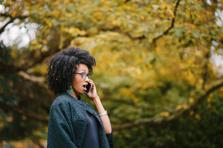 Young surprised black woman talking on cellphone outside at the park on autumn season. Amazed fashionable girl with afro hair. Stok Fotoğraf