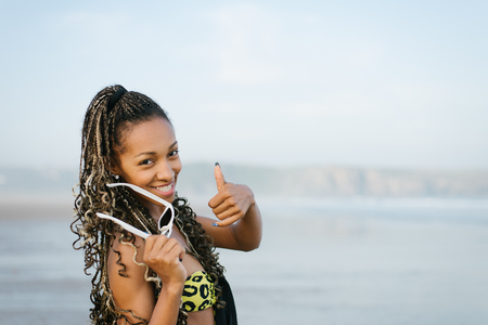 Stylish woman smiling and holding sunglasses towards the sea on summer vacation. Black beautiful model with dreadlocks doing thumbs up success gesture. Stock Photo