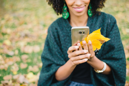Detail of woman using smartphone in autumn at the park. Black female holding cellphone and fall leaves.