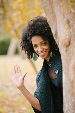 Black beautiful woman waving behind a tree in autumn at city park. Banco de Imagens