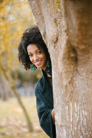 Black beautiful woman enjoying leisure at city park in autumn.
