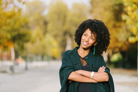 Black pensive woman in autumn at city park looking up and smiling. Afro hair style.