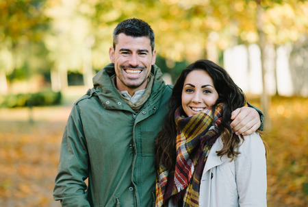 Lovely young couple in autumn at the park. Romantic man and woman in love outdoor in fall season. Banco de Imagens