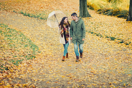 Lovely young couple in love walking in autumn at the park. Romantic man and woman outdoor in fall season. Фото со стока