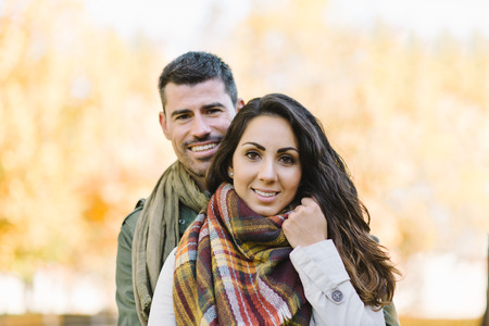 Lovely cheerful young couple portrait in autumn at the park.