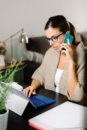 Female entrepreneur working from home. Professional woman calling on smartphone and using convertible tablet. Stock Photo