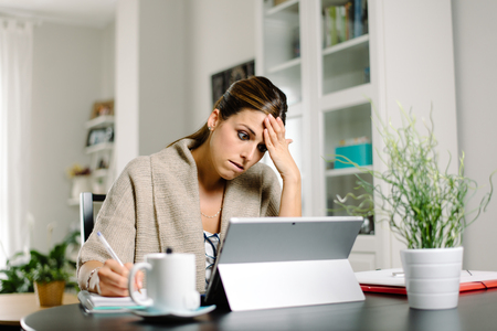 Stressed female entrepreneur working from home with digital tablet. Afraid woman in trouble.