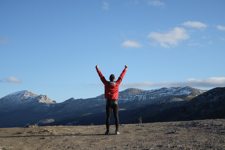 Back view of successful sporty man celebrating training goals towards and freedom on the mountain and sky in late winter. Stock Photo