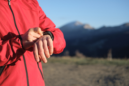 Detail of athlete using sport watch for timing outdoor running workout on a mountain in late winter. 版權商用圖片