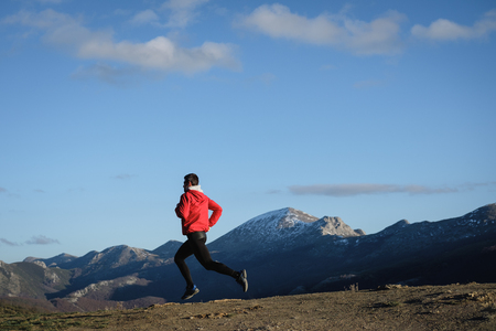 Sporty man running cross country outdoor on the mountain. Athlete training and exercising in late winter.