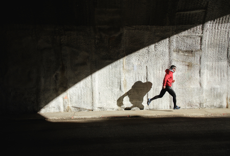 Powerful athlete sprinting and running. Man training and casting shadow in a wall.