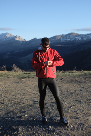 Runner taking a break for timing outdoor workout on the mountain in late winter.