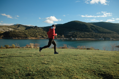 Sporty man running outdoor on the mountain. Athlete training and exercising in late winter.