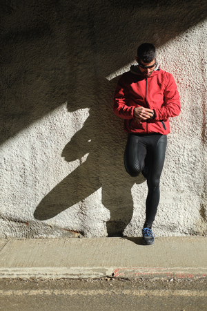 Runner leaning on a wall for taking a rest and timing workout. 版權商用圖片