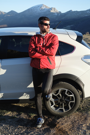 Athlete taking a break after outdoor workout on the mountain in late winter. Sporty man leaning on his car.