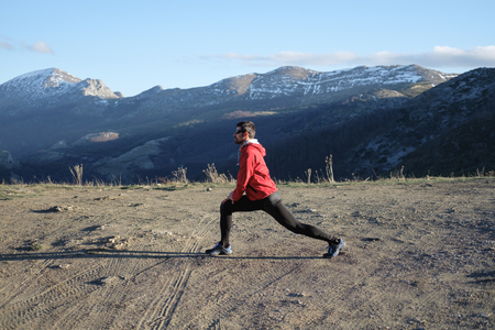 Man exercising and stretching during late winter workout in the mountain.
