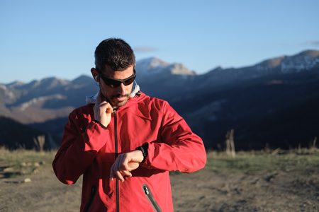 resting heart rate: Athlete taking a break for checking the pulse after cross country running outdoor on a mountain in late winter. Stock Photo