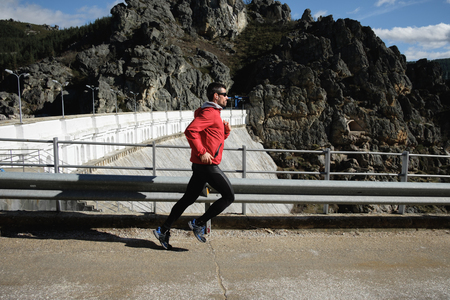 Sporty man running on a mountain road in late winter. Healthy outdoor workout.