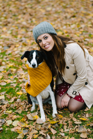 Woman and dog portrait in autumn at the park. Banco de Imagens