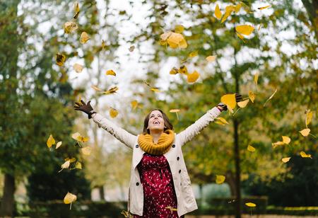행복 한 임신 한 여자 임신 및 가을 시즌을 던지고 공원에서 공기를 나뭇잎.