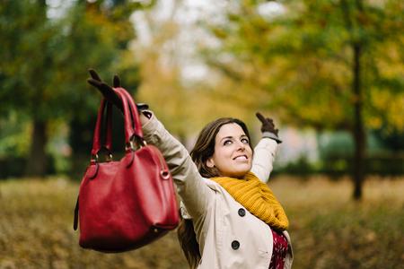 至福の女性が公園で秋に腕を上げます。幸福と成功のコンセプトです。 写真素材