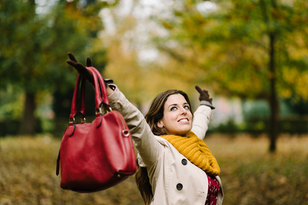 Blissful woman raising arms in autumn at the park. Happiness and success concept. Reklamní fotografie