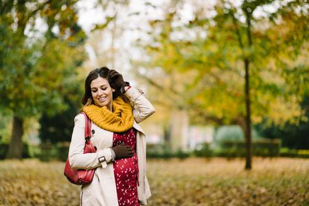 スカーフと秋に彼女の腹に触れるレインコート幸せな妊娠中の女性。ブルネットの女性は、レインコートと暖かい黄色のスカーフを身に着けていま