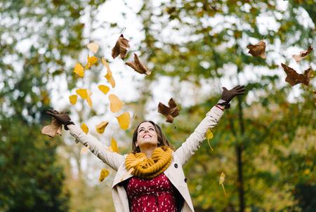 행복 한 여자 던지고 공원 에서을 시즌을 즐기고 공기 나뭇잎.