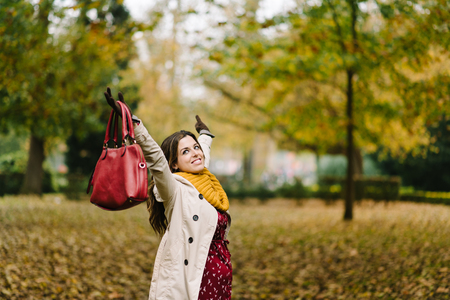 幸せな妊娠中の女性は、公園で妊娠と秋の季節を楽しんでいます。