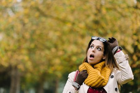 表現力豊かな女性と秋に見上げると口を開いてびっくり。 写真素材