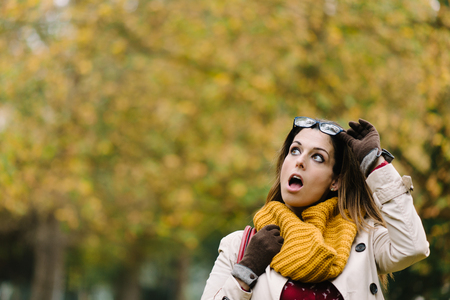 Amazed expressive woman opening mouth and looking up in autumn.