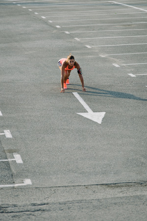 Female athlete ready for running and sprinting on urban asphalt. Sporty woman training in the city in summer.