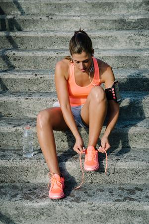 Vrouwelijke atleet zich klaar voor stedelijke fitness en looptraining. Sportieve vrouw die sportschoeisel rijpt.