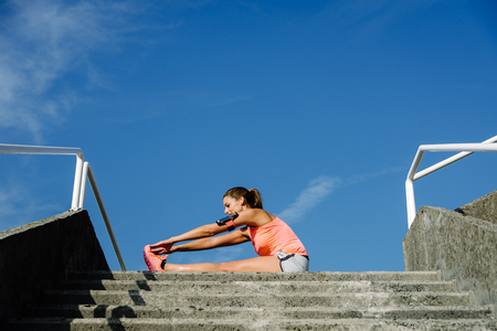 Sporty woman stretching for cooling down after running and exercising outside. Athlete exercising against blue sky background.