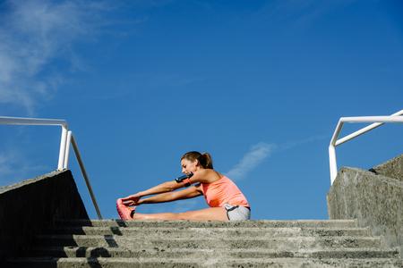 Mulher desportiva, estendendo-se para arrefecer depois de correr e exercitar fora. Atleta que exercita contra o fundo do céu azul. Foto de archivo - 89520220