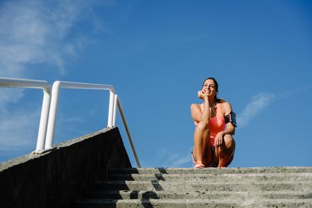 Donna sportiva fitness prendendo una pausa e ascoltare musica. Addestramento allegro dell'atleta di estate. Archivio Fotografico