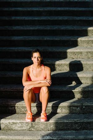 Sporty young woman sitting on stairs for resting after outdoor urban running and fitness workout.