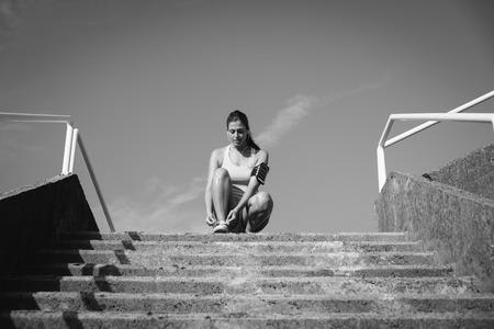 Vrouwelijke atleet die klaar voor buiten het lopen en uitoefenen worden. Sportieve vrouw het luisteren muziek en het rijgen van sportschoenen tegen blauwe duidelijke hemelachtergrond. Stockfoto