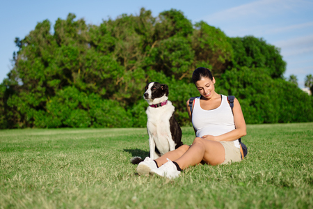 夏のリラックスした妊娠中の女性は彼女の犬と公園で散歩します。