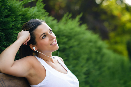Close up of sporty woman relaxing and listening music at the park. Pensive female looking up and daydreaming.