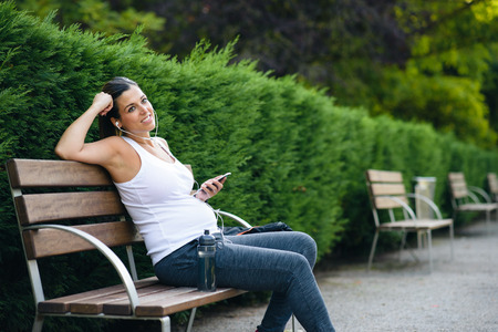 Relaxed sporty pregnant woman listening music while sitting in a park bench for resting after outdoor healthy fitness workout.