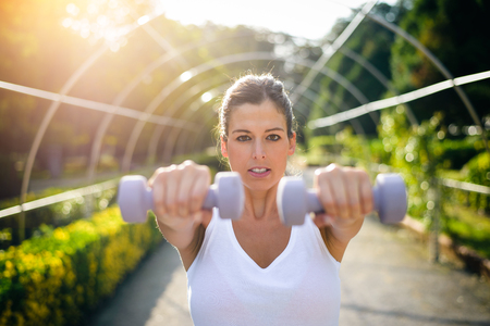 Motivated fitness woman working out outdoor with dumbbells. Shoulder front raises exercise.